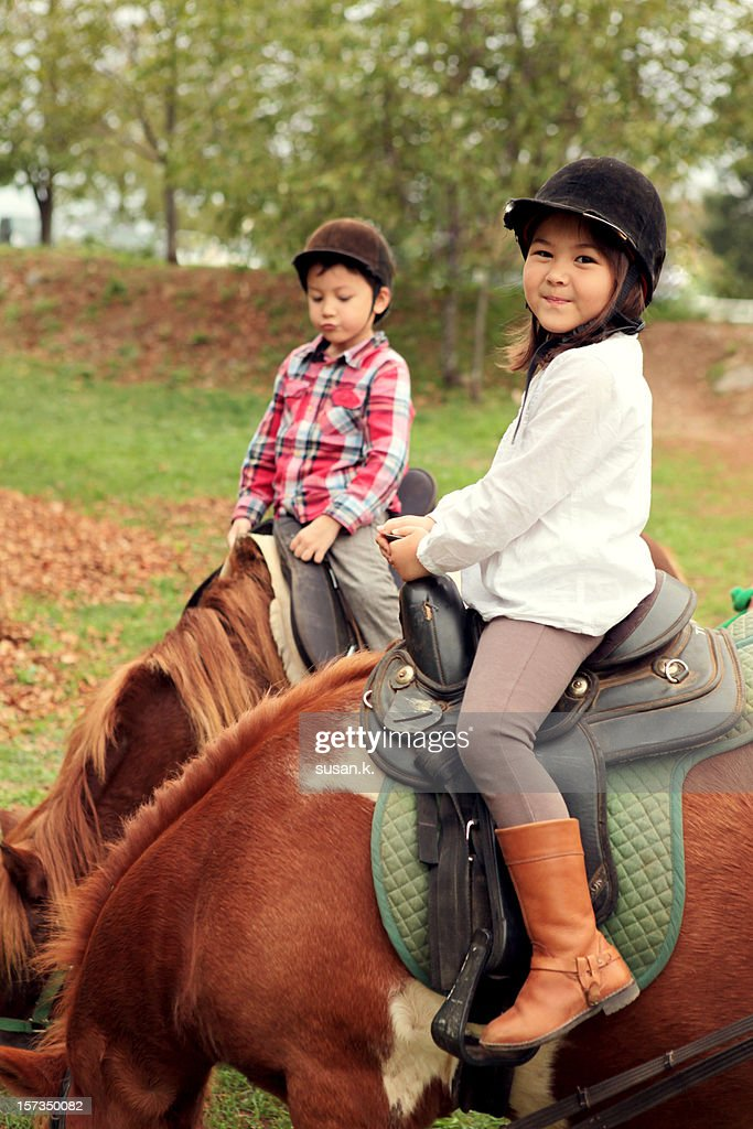 Boy and girl having fun riding ponies.