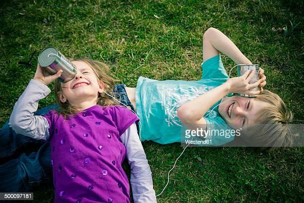 Boy and girl having fun with tin can phone
