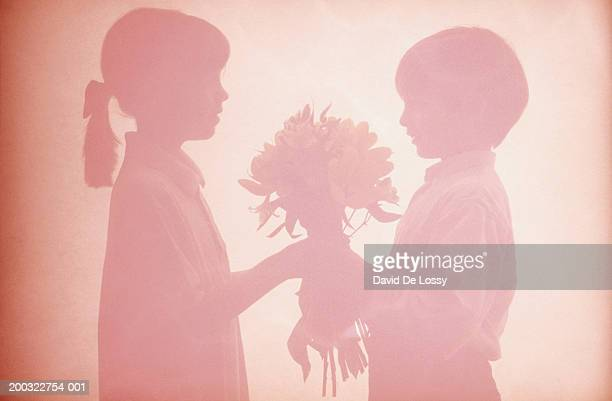 Boy and girl holding bouquet behind curtain, side view