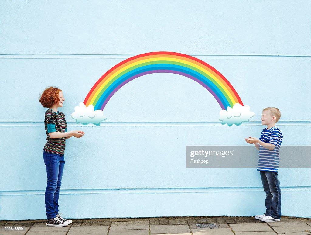 Boy and girl holding cartoon rainbow