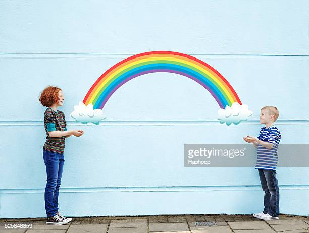 Boy and girl holding cartoon rainbow