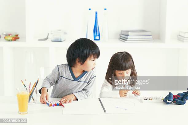 Boy and girl (3-4) holding crayons sitting on table, boy looking at crayon