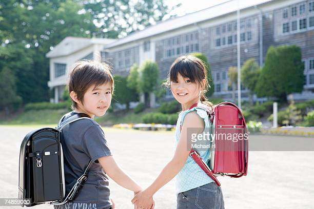 Boy and girl (7-9) holding hands in school playground, portrait