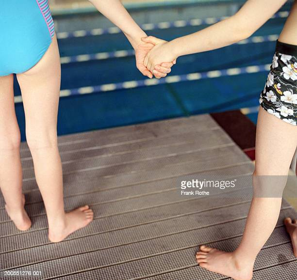 Boy and girl (6-11) holding hands on diving board, close-up, low section