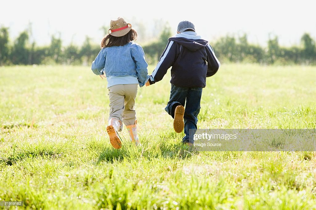 Boy and girl holding hands, running on field : Stock Photo