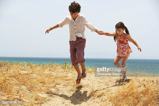 Boy (7-9) and girl (2-4) holding hands, skipping on dunes