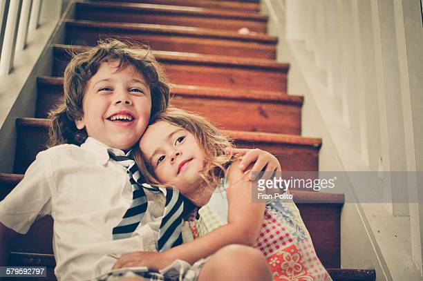 A boy and girl hugging on a staircase in their hom