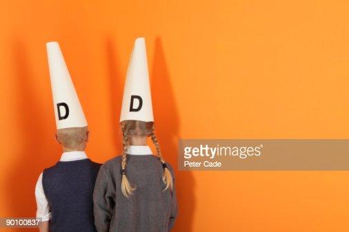 boy and girl in corner wearing dunces hat : ストックフォト