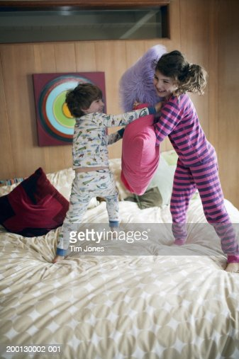 Boy and girl in pyjamas having pillow fight on bed stock for Boys and girls in bed