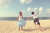 Boy and girl jumping & dancing on sandy beach.