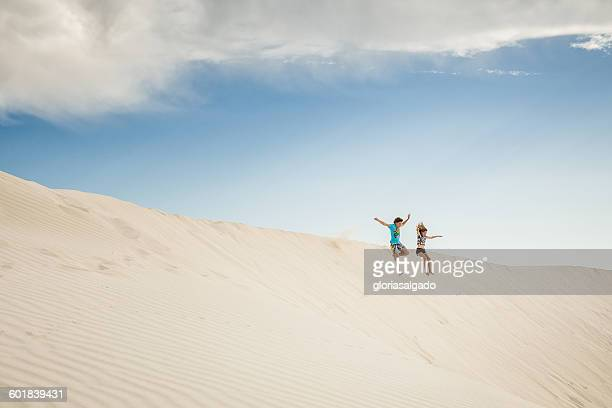 Boy and girl jumping in sand dunes, Green Head, Western Australia, Australia