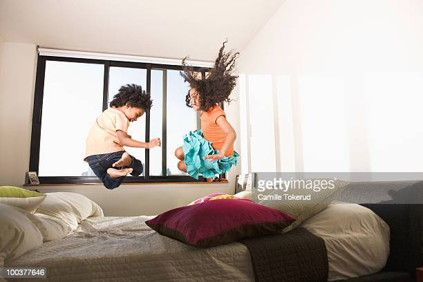 Boy and Girl Jumping on Bed