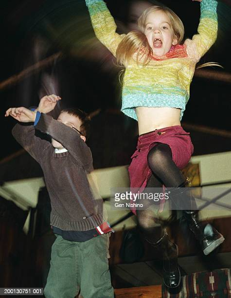 Boy and girl (5-9) jumping (blurred motion)
