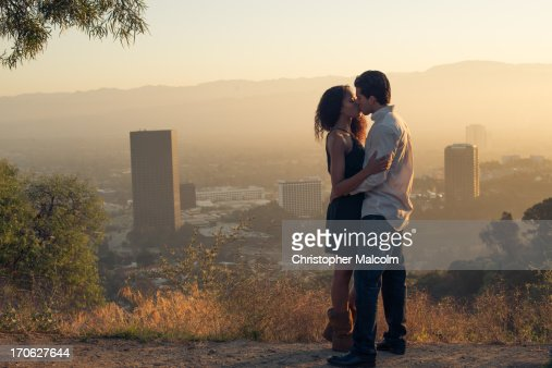 Boy and girl kiss at sunrise
