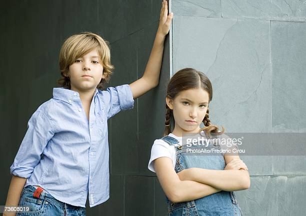 Boy and girl, leaning against corner of wall, portrait