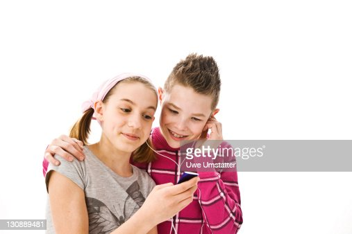 Boy and girl listening to music together with headphones on an iPod : Stock Photo