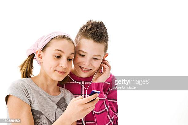 Boy and girl listening to music together with headphones
