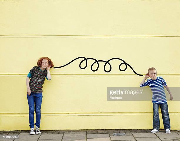 Boy and girl listening via cartoon wire