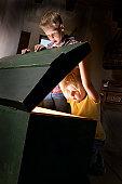 Boy and girl (4-6) looking inside illuminated large box