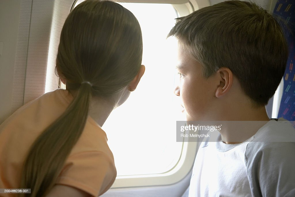 Boy (9-11) and girl (6-8) looking out window on airplane