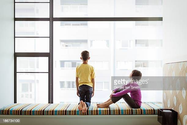 Boy and girl looking out window