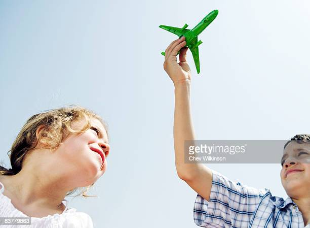 Boy and girl looking up at toy plane