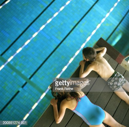 Boy and girl (6-11) lying at edge of swimming pool, elevated view : Stock Photo
