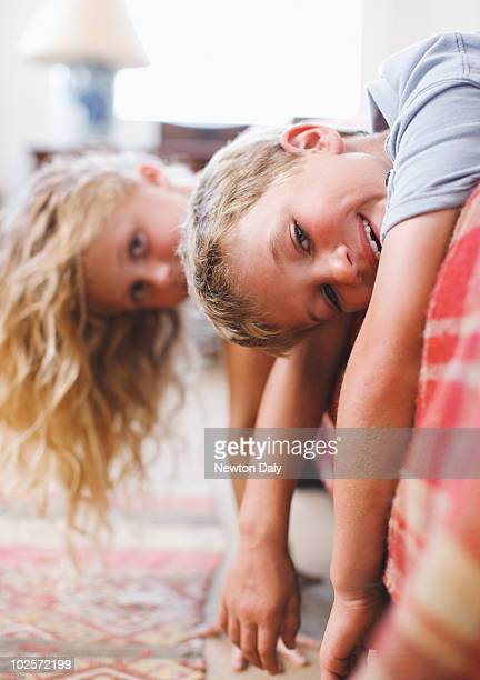 Boy and girl lying on a bed with arms outstretched