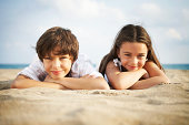 Boy and girl (8-10) lying on beach, smiling, close-up, portrait
