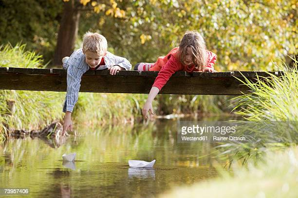 Boy (10-13) and girl (7-9) lying on bridge, watching paper boats in water