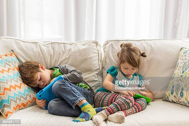 Boy and girl lying on couch playing with digital tablets
