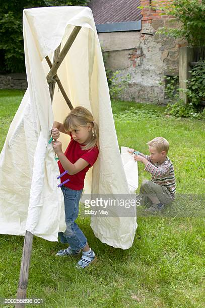 Boy and girl (4-6) making cubby house in garden