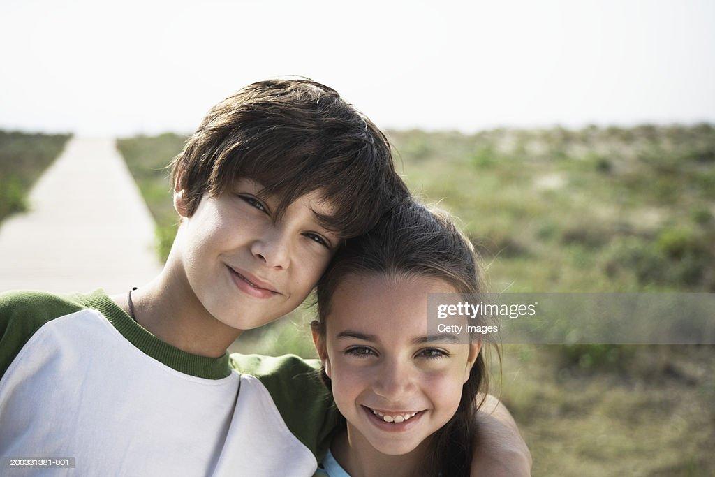 Boy and girl (8-10) on beach boardwalk, close-up, portrait : Stock Photo