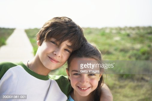 Boy and girl (8-10) on beach boardwalk, close-up, portrait