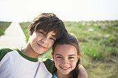 Boy and girl (8-10) on beach boardwalk, close-up, portrait