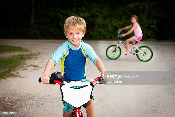 Boy and girl on bicycles looking at camera smiling