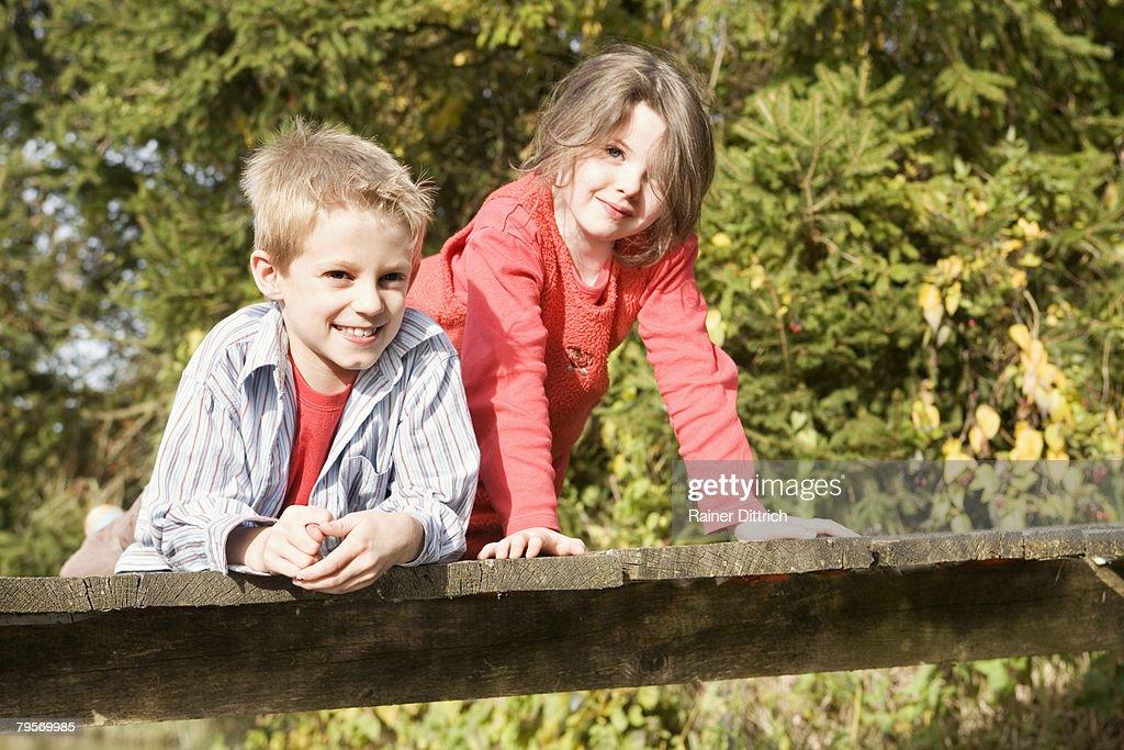 Boy (10-12) and girl (7-9) on bridge : Stock Photo