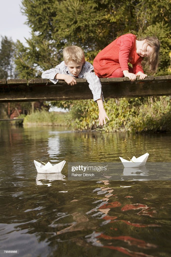'Boy (10-12) and girl (7-9) on bridge, watching paper boats in water' : Stock Photo