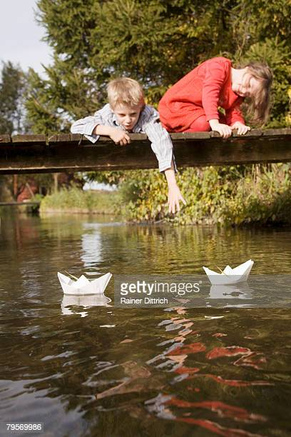 'Boy (10-12) and girl (7-9) on bridge, watching paper boats in water'