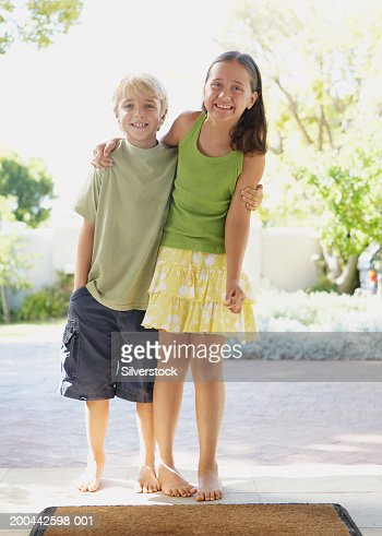 Boy and girl (6-8) on door step with arms around each other, smiling : Stock Photo