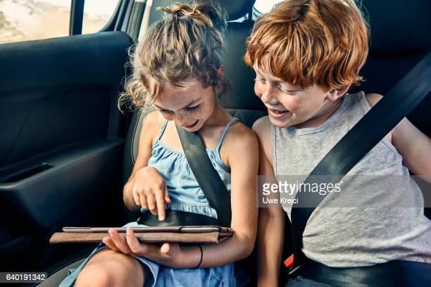 Boy and girl on rear seat of car, playing on tablet