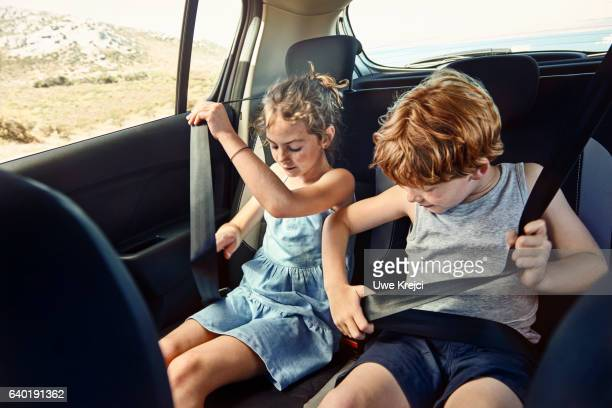 Boy and girl on rear seat of car, putting safety belts on