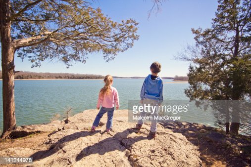 Boy and girl on rock bluff : Stock Photo