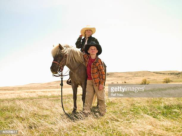 Boy and girl on Shetland pony on prairie