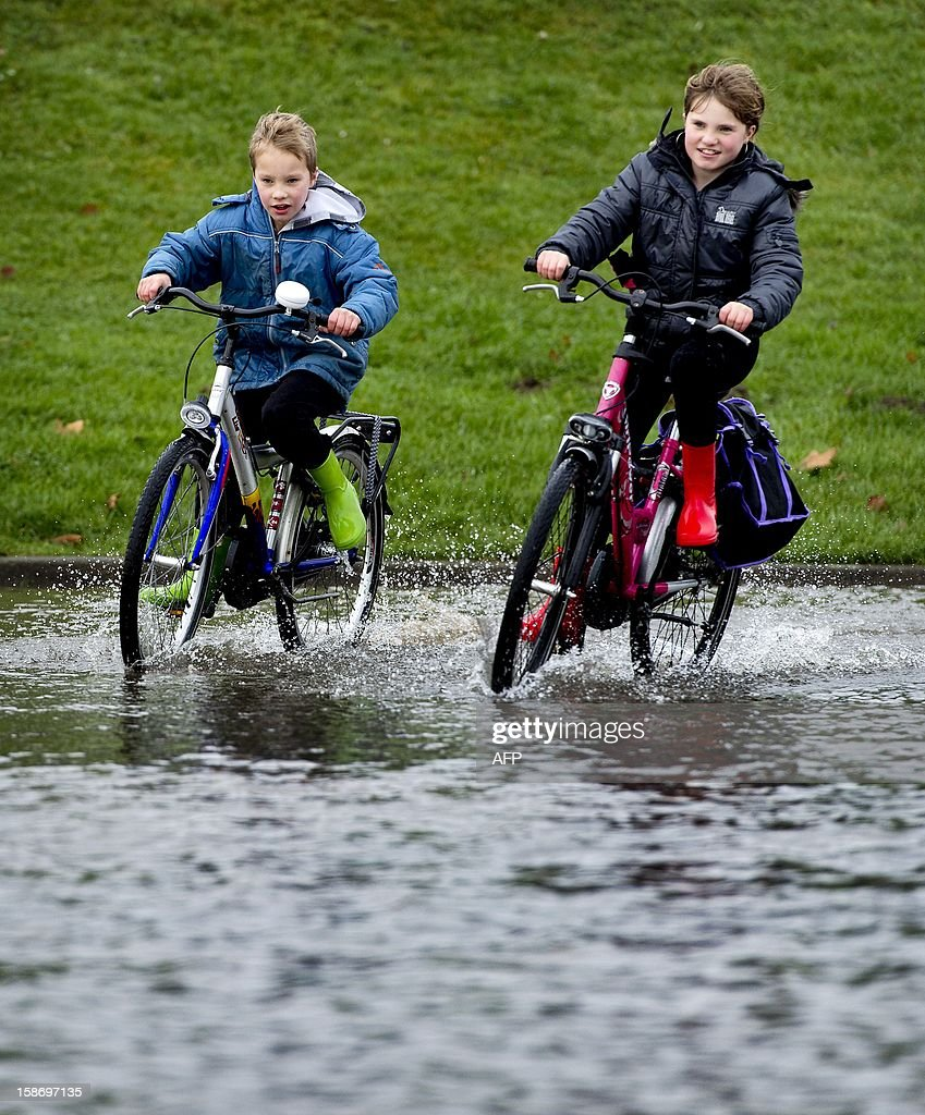 A boy and girl on their bikes ride on a flooded quay of the river Waal in Tiel, central Netherlands, on December 24, 2012. The high water level, due to heavy rainfall, has caused problems in several places in the Netherlands. AFP PHOTO/ANP KOEN VAN WEEL netherlands out