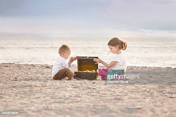 Boy and Girl Open Treasure Chest on Beach