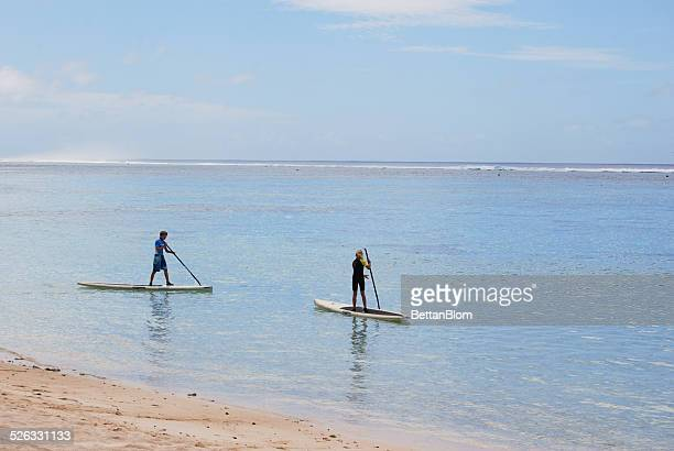 Boy and girl paddle boarding, Cook Islands
