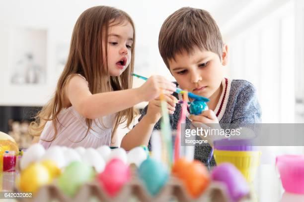 Jungen und Mädchen bemalen von Ostereiern