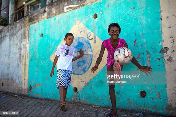 A boy and girl play football in the Chacara do Ceu favela or shantytown on November 2 2013 in Rio de Janeiro Brazil The favela was previously...