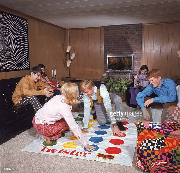 A boy and girl play the game Twister as other young people watch in a paneled living room circa 1968
